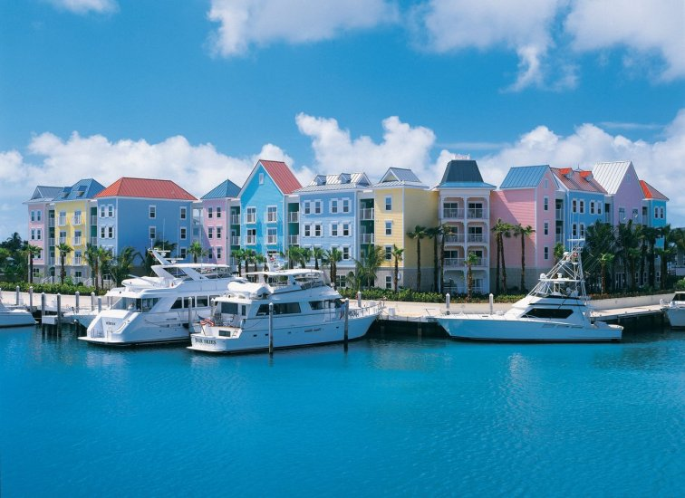Beautiful blue water with 3 yachts anchored outside of pink, yellow and blue buildings