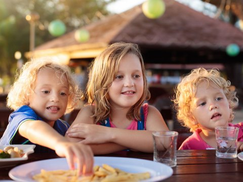 Kids Eating at Resort; Courtesy of FamVeld/Shutterstock.com