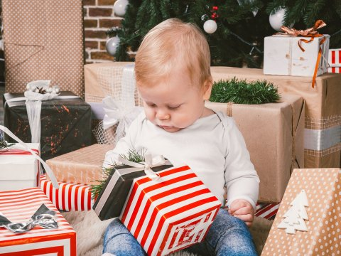 Infant Opening Holiday Gifts; Courtesy of fotoliza/Shutterstock.com