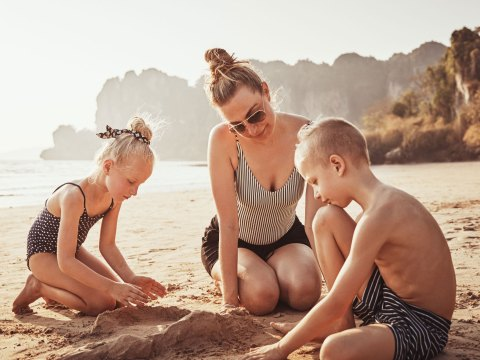 Mom In One Piece Bathing Suit with Kids on Beach; Courtesy of Flamingo Images/Shutterstock.com