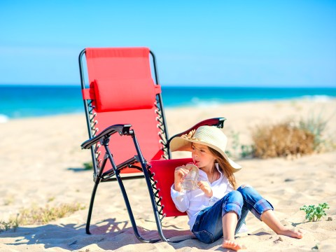 little girl in a beach hat sits on the beach near the chair and drinks fresh juice; Courtesy of fotosaga/Shutterstock
