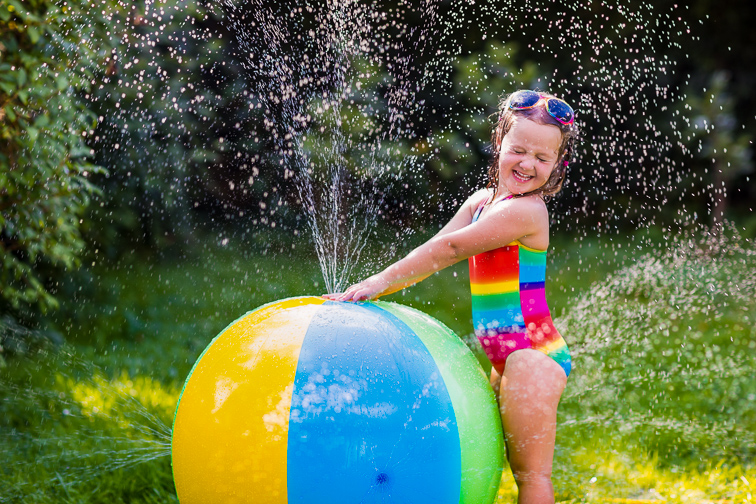 Funny laughing little girl in a colorful swimming suit playing with toy ball garden sprinkler with water splashes having fun in the backyard on a sunny hot summer vacation day. ; Courtesy of Famveld/Shutterstock