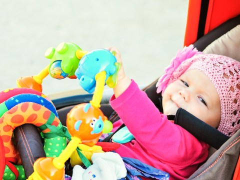 happy baby in the stroller playing toys; Courtesy of Elena Stepanova/Shutterstock