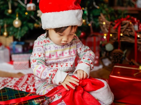 toddler baby girl wearing santa claus costume looking for gift in front of christmas tree - Image ; Mcimage /Shutterstock