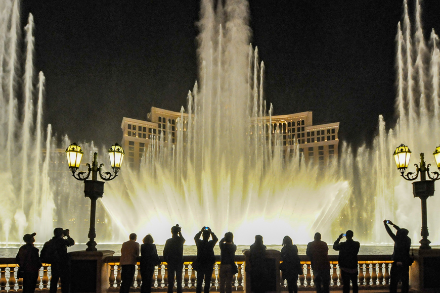 People look at night view of the fountain of Bellagio, Las Vegas, ; Courtesy of Bumble Dee /Shutterstock