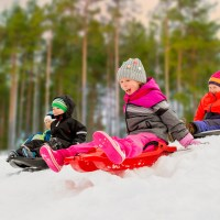 group of happy little kids sliding on sleds down snow hill in winter ; Courtesy of Syda Productions/Shutterstock
