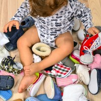 Toddler playing with a lot of baby shoes. ; Courtesy of Iulian Valentin/Shutterstock