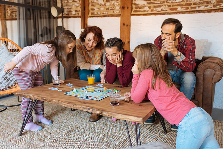 Happy family at home in the couch playing classic table games; Courtesy of David Prado Perucha/Shutterstock