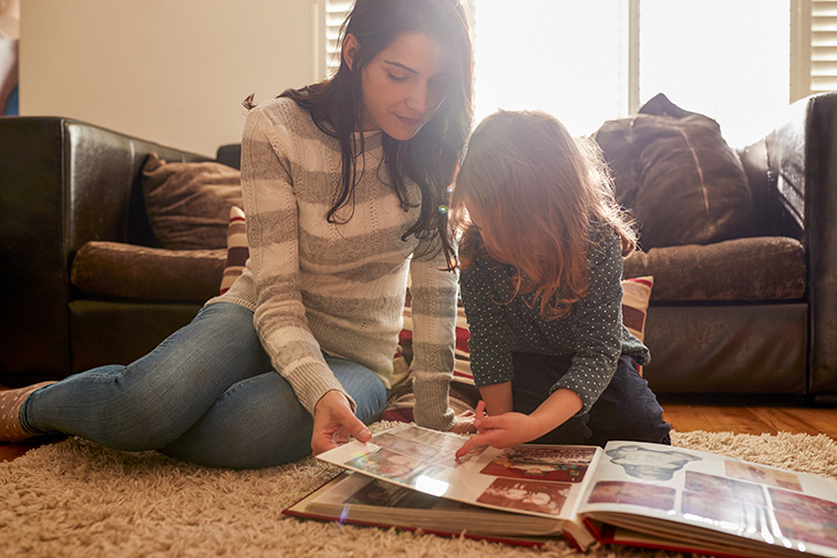 Mother And Daughter At Home Looking Through Photo Album; Courtesy of Monkey Business Images/Shutterstock