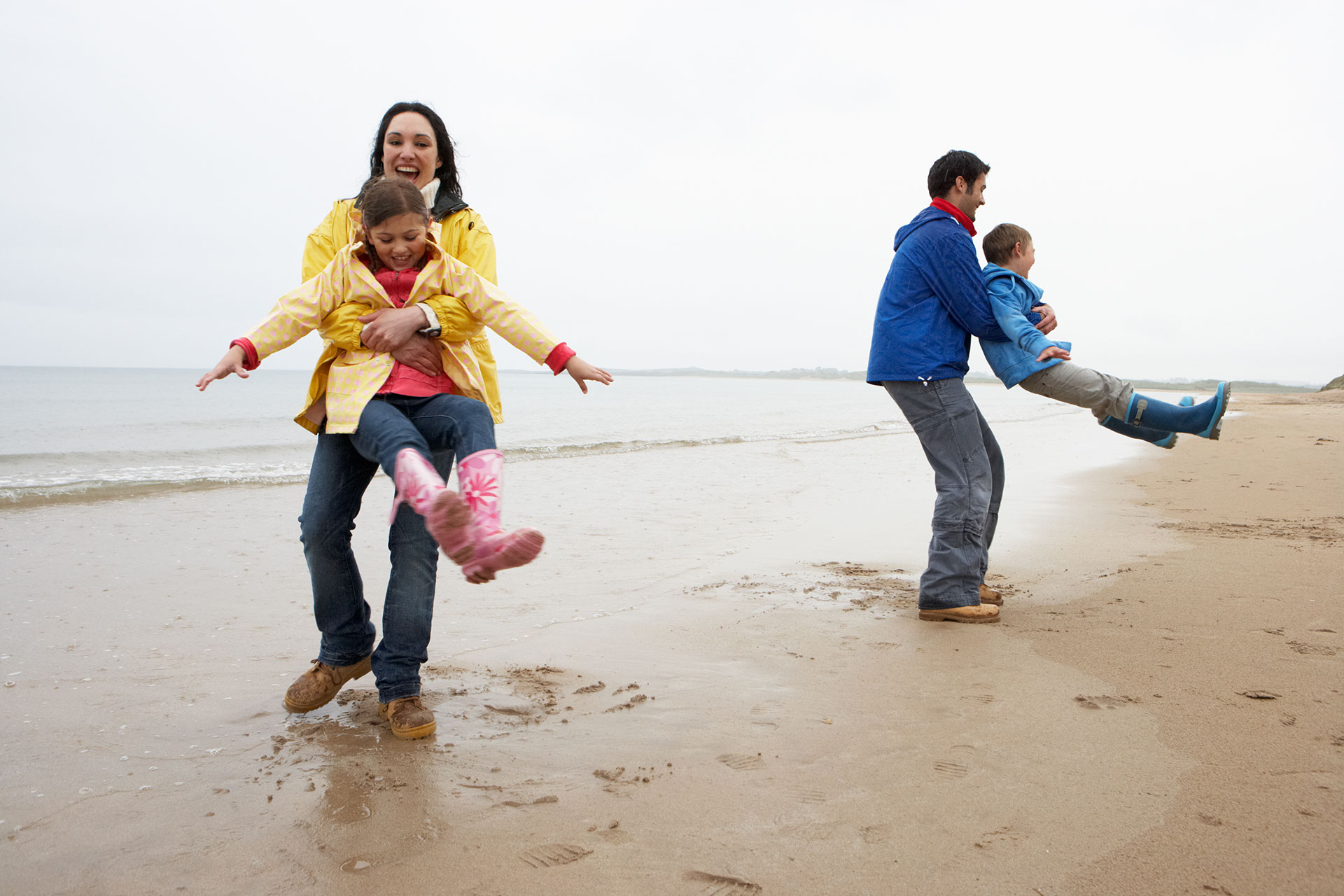 Family Playing in the rain on the Beach