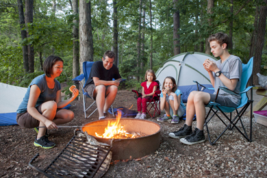 A family having fun while cooking their meal over a fire.