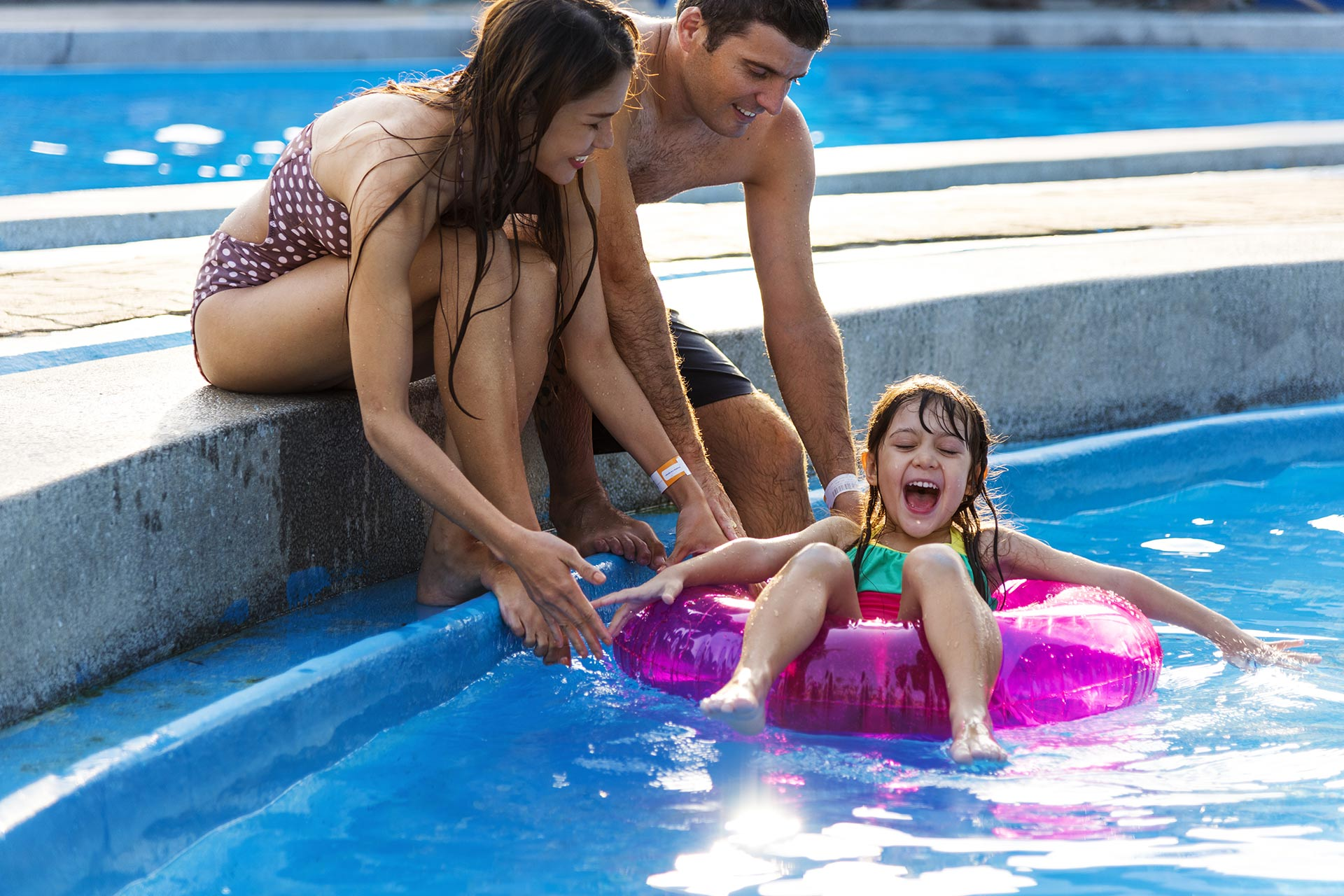 A family enjoying some time in the pool in the midst of their vacation.