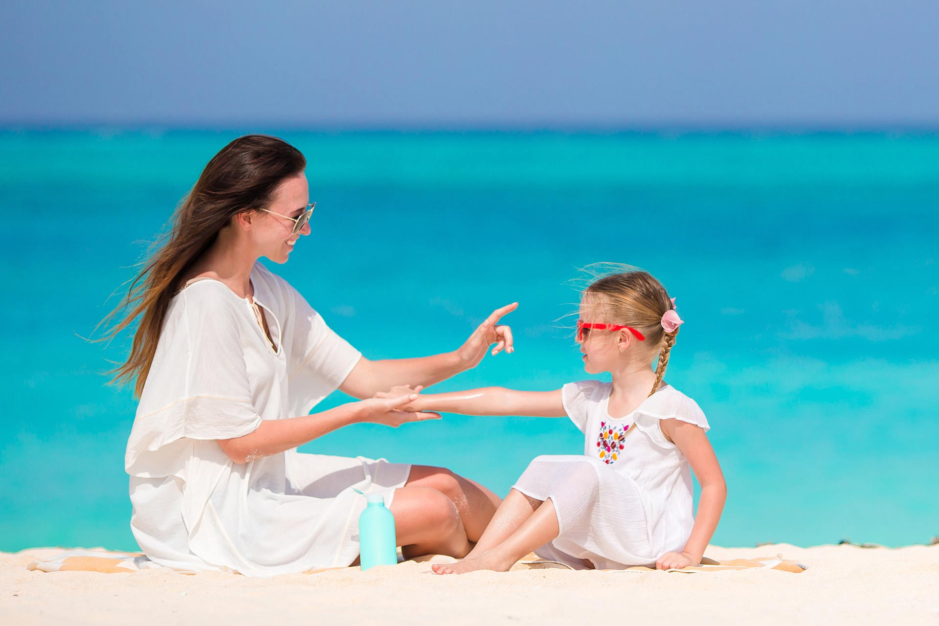 A mom applying sunscreen on her daughter.