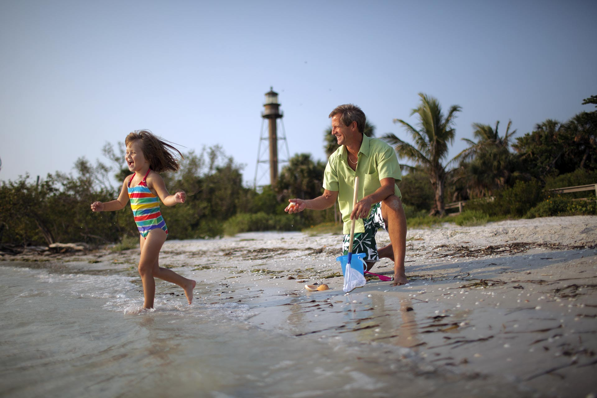 A little girl and her father playing on the beach on Sanibel Island, Florida.