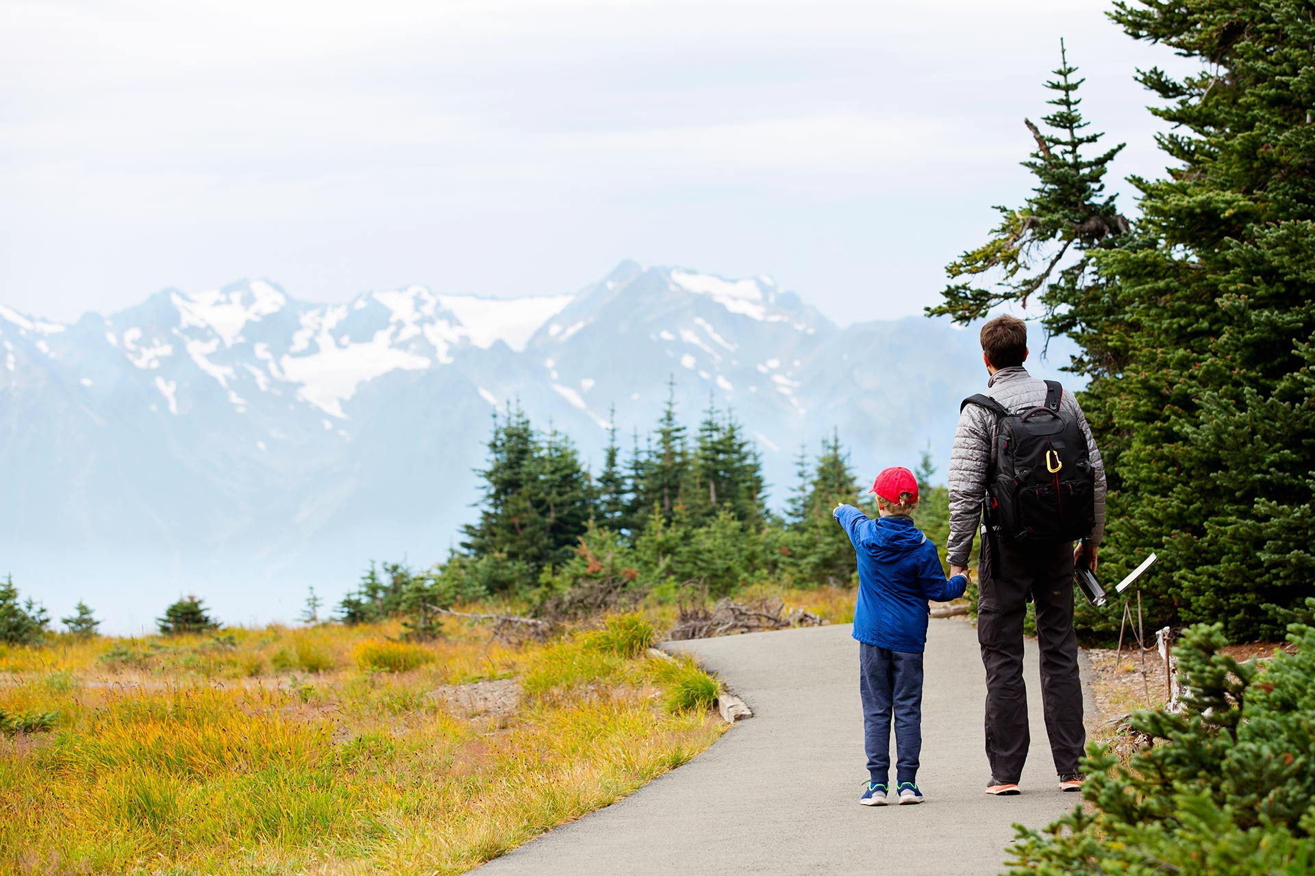 A father and son taking in the beautiful views at Olympic National Park in Washington.