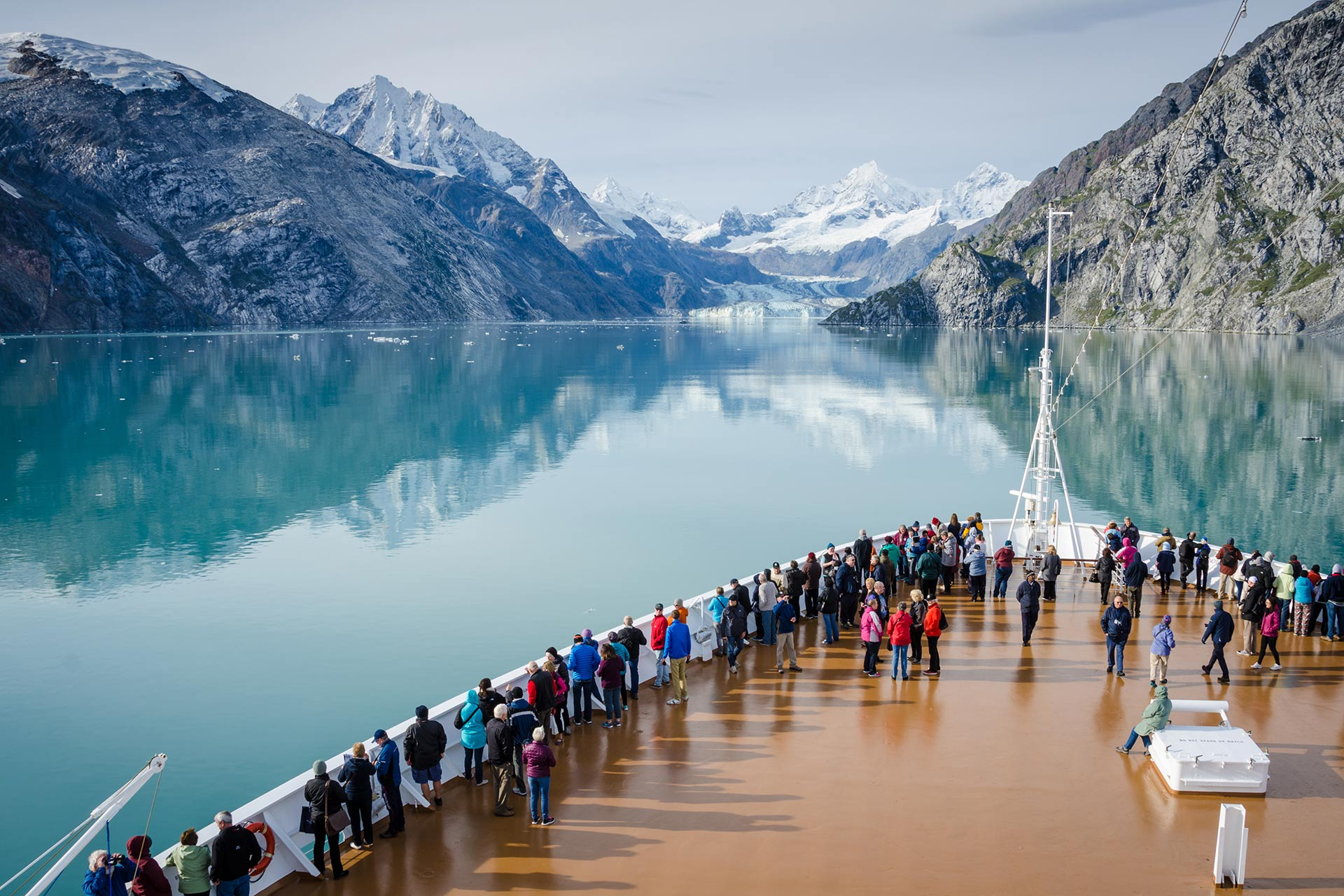 A group of people onboard a cruise ship enjoying the magnificent views of Glacier Bay in Alaska.