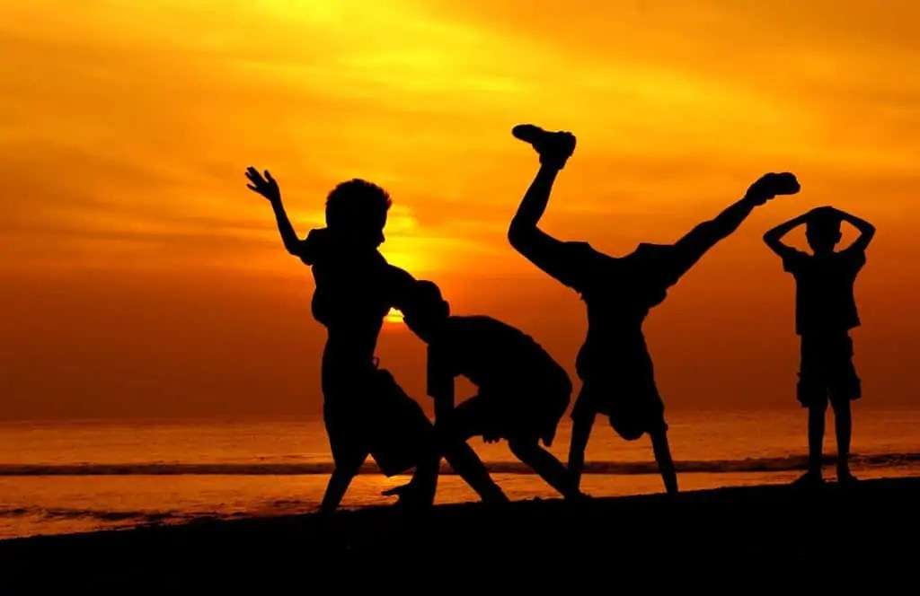 Children Playing At Sunset On Beach Famlii