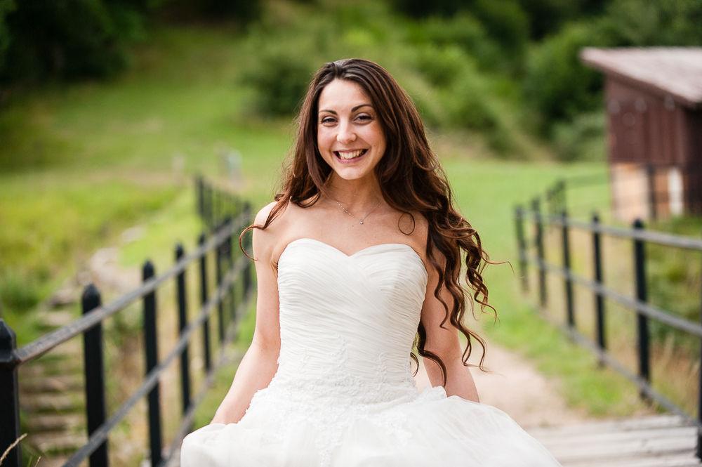 Portrait d'une mariée en extérieur en couleur tenant sa robe avec un grand sourire.