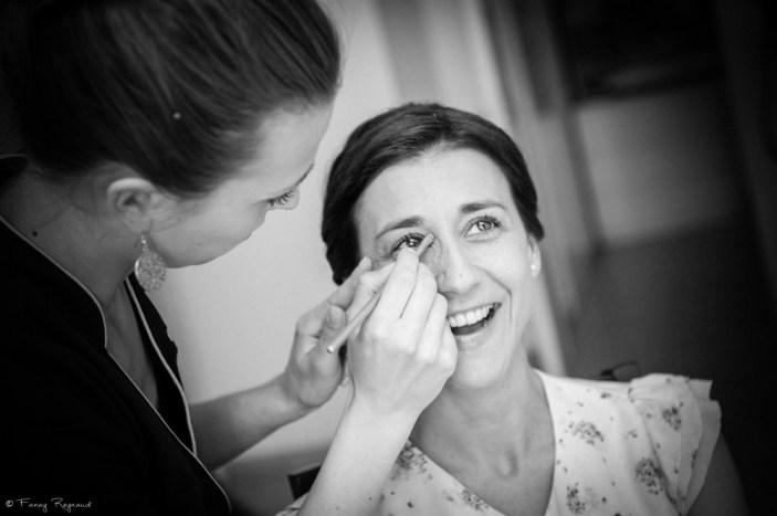 La mariée sourit pendant la séance de mariage avant son mariage. Photographie noir et blanc prise en auvergne par un photographe professionnel.