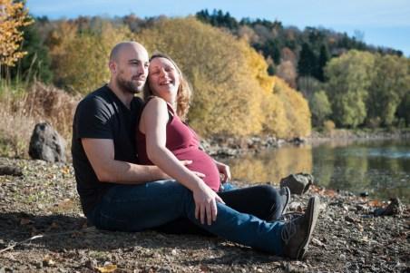 Photographie professionnelle d'un couple attendant un enfant assis au bord du lac de la cassière dans le puy-de-dome. Séance en extérieur en automne par Fanny Reynaud photographe professionnelle à clermont-ferrand.
