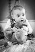 Photo d'une petite fille avec un gros ours en peluche, en noir et blanc et en lumière naturelle, réalisée lors d'un shooting à domicile près de clermont-ferrand par un photographe professionnel. © Fanny Reynaud.