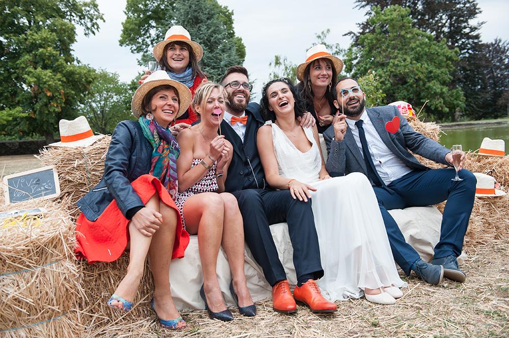 Photo de groupe de mariage : explosion de rires et accessoires (moustaches, lunettes) sur une botte de paille , au chateau de féligonde à sayat en auvergne. Photo couleur par un photographe professionnel de clermont-ferrand.