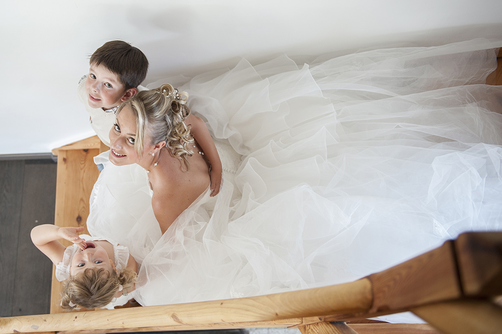 Photographie d'une mariée avec deux enfants, vue en plongée, moment intime après l'habillage.