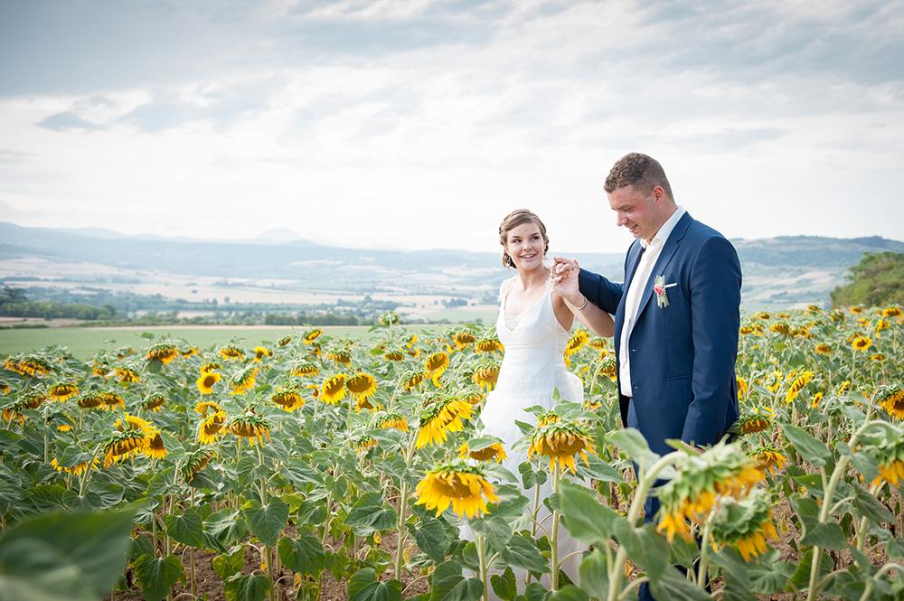 Photo de couple de mariage dans un champ de tournesols à montpeyroux, près de clermont-ferrand, en auvergne. Photographie couleur par un photographe professionnel.