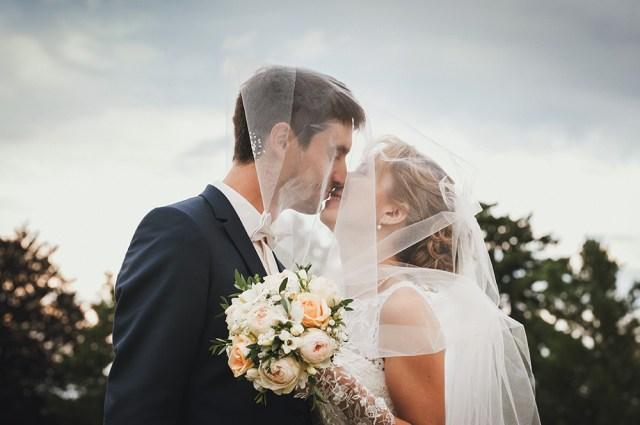 photo de couple spontanee au chateau de feligonde a sayat, sous le voile de la mariee