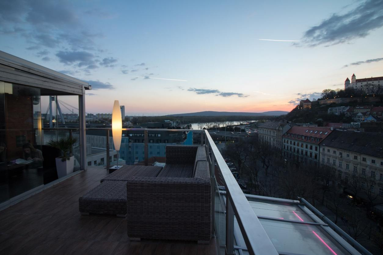 a-rooftop-terrace-with-outdoor-seating-and-lights-at-sunset-skybar-bratislava