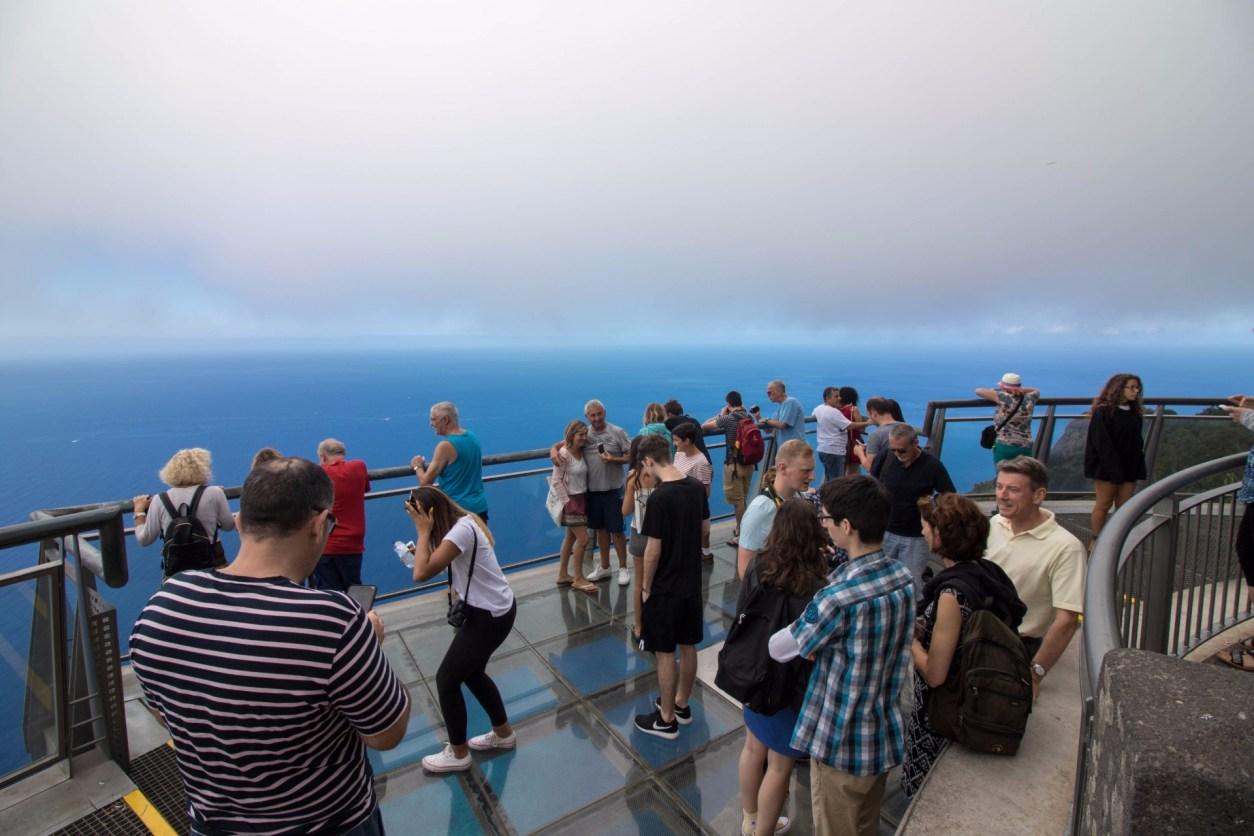 туристы собрались на стеклянной платформе с видом на море Кабо Жирао Мадейра
