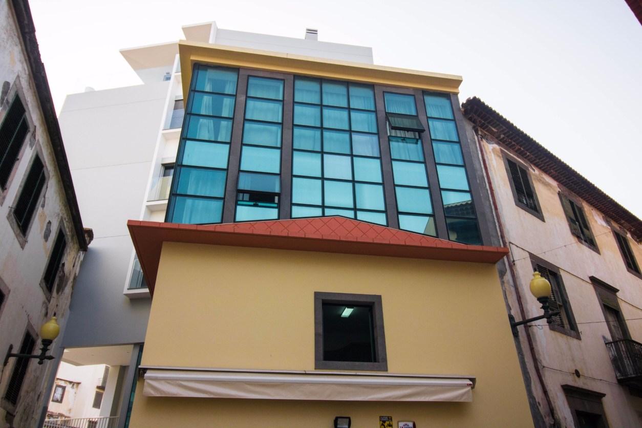 желтое здание с современными квартирами над ним с синими тонированными окнами Мадейра