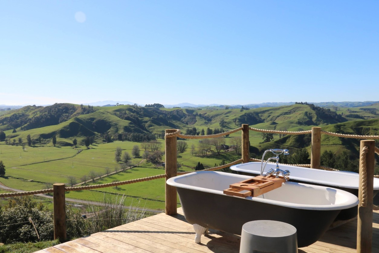 two-bath-tubs-sat-on-a-ledge-looking-out-to-beautiful-green-rolling-hills-at-waitomo-hilltop-glamping