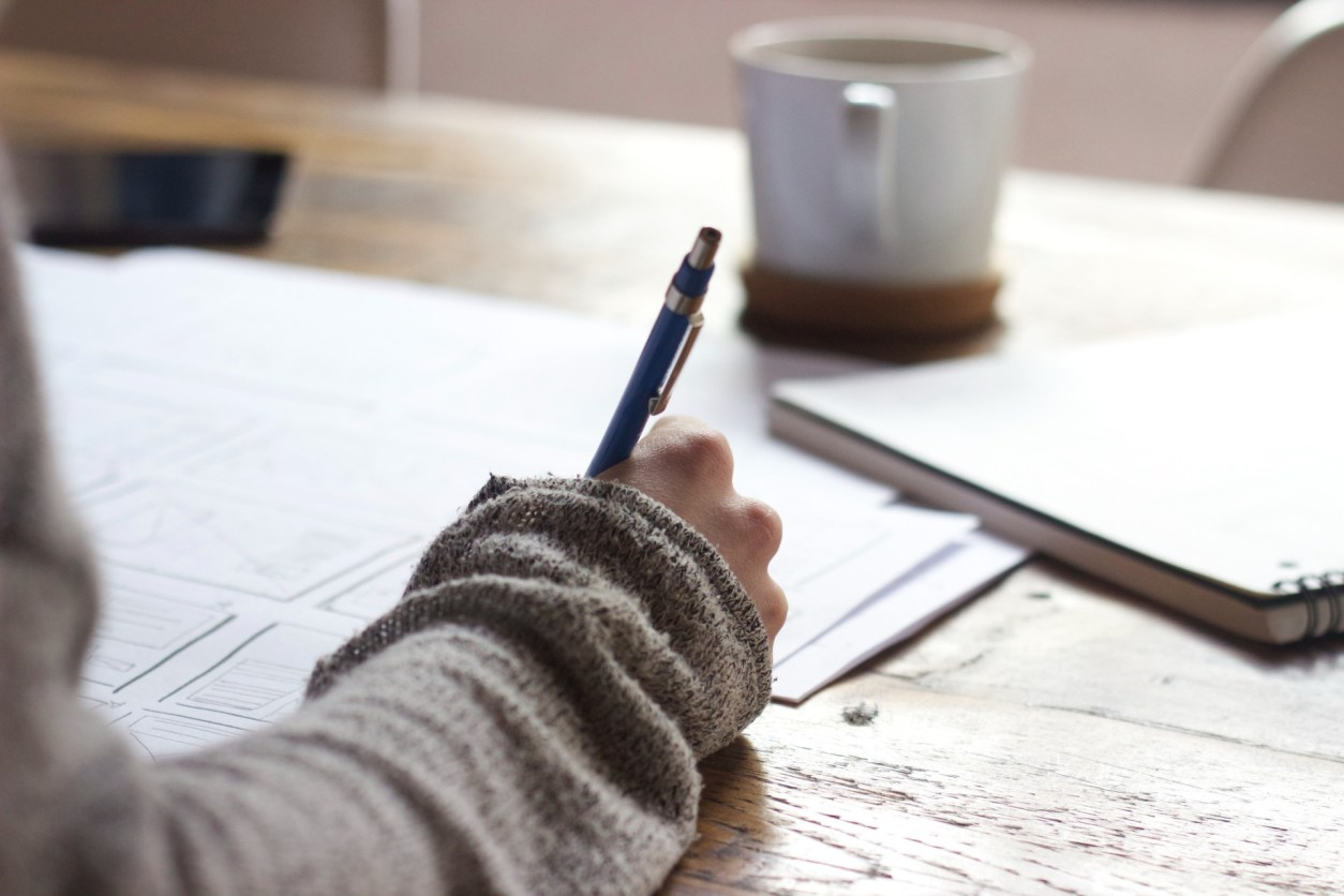 Writing with a pen on a piece of paper on a table with a notebook and a mug How to Get Into Marketing with an English Degree