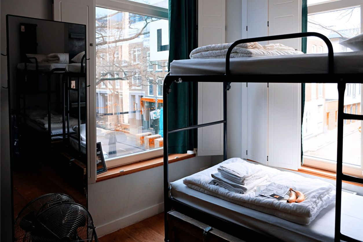 bunk-beds-with-white-linen-and-towels-in-a-hostel-room-in-a-city-sustainable-travel-tips