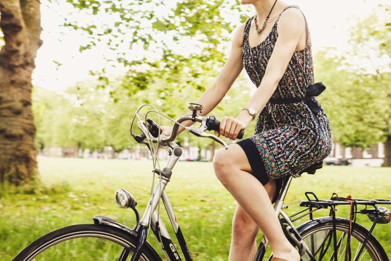 woman-wearing-floral-dress-cycling-on-bike-in-green-park-with-grass-and-trees-in-the-background-sustainable-travel-tips