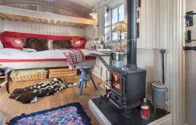 wood-stove-desk-and-sofa-bed-in-cute-shepherds-hut-lake-district-airbnb-canopy-and-stars