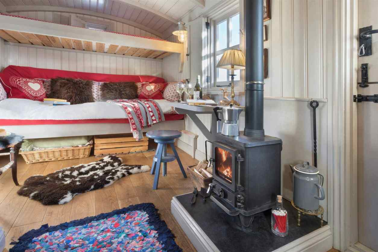 wood-stove-desk-and-sofa-bed-in-cute-shepherds-hut-lake-district-airbnb-canopy-and-stars-unusual-romantic-weekend-breaks-uk
