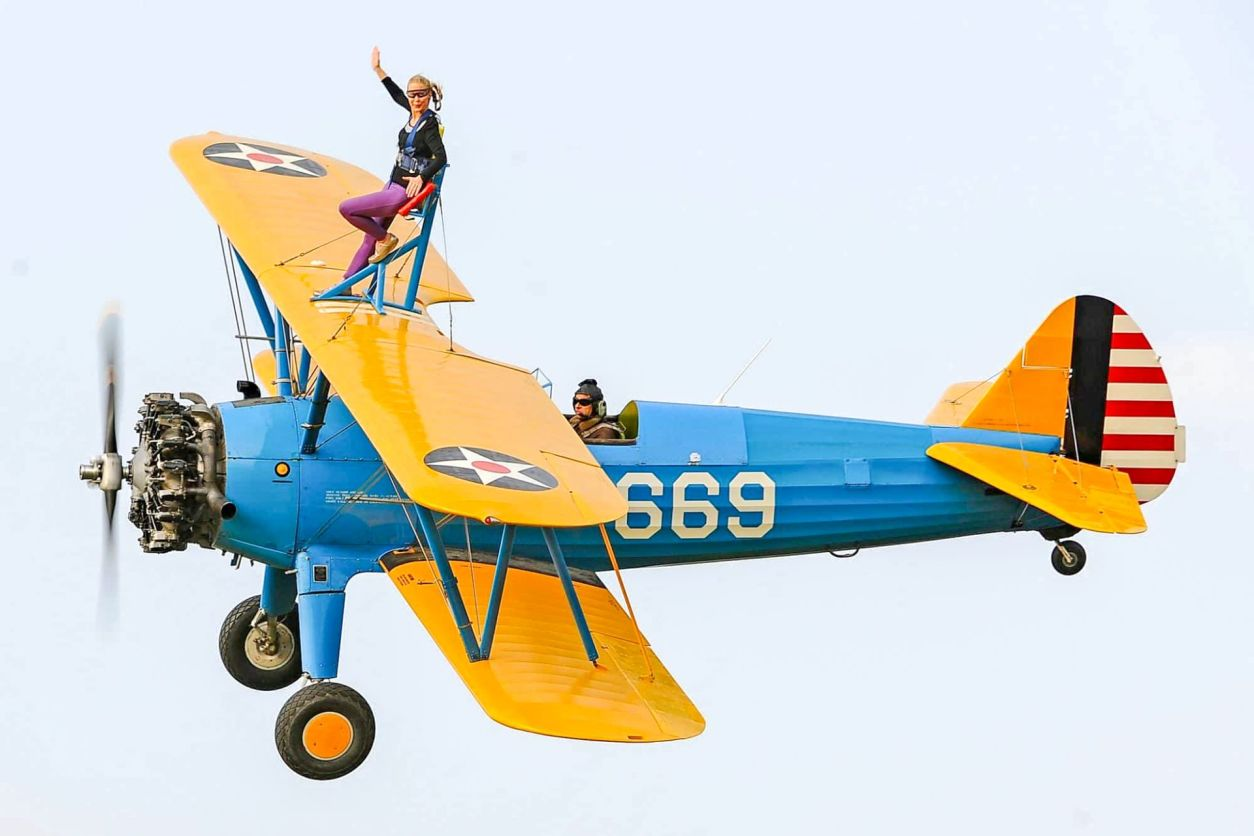 woman-strapped-to-the-top-of-a-plane-flying-in-the-air-walking-on-the-wing-of-a-plane-in-the-uk-adrenaline-junkie-bucket-list