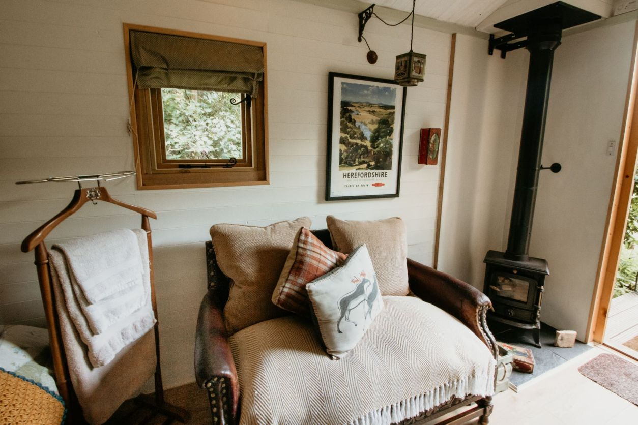 cosy-rustic-living-area-with-fire-in-prothero-shepherds-hut-the-moon-and-i-glamping-with-hot-tub-herefordshire