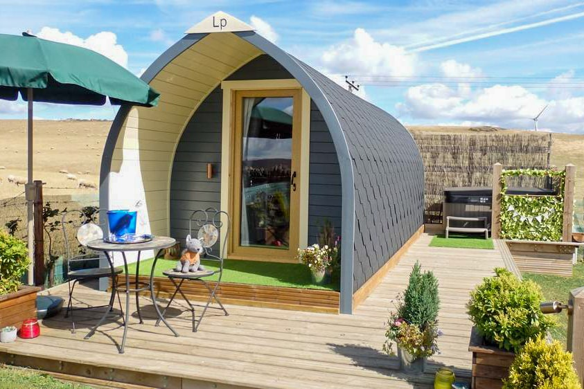 glamping-pod-sat-on-decking-in-field-with-hot-tub-table-and-chairs-the-holiday-pod-sheffield-glamping-with-hot-tub-yorkshire