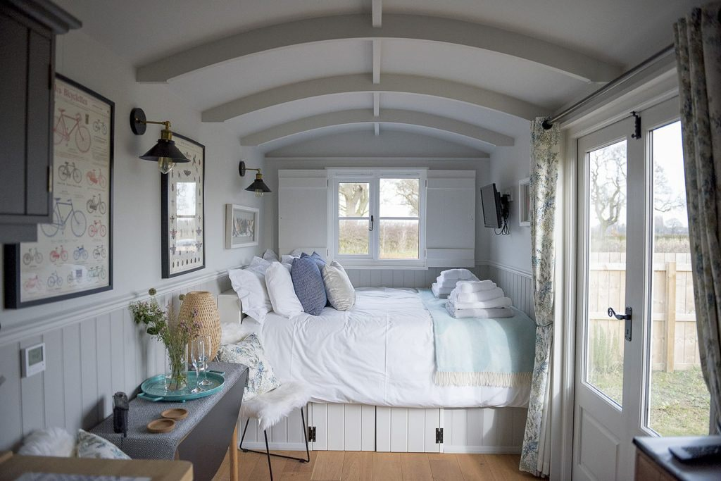 interior-of-a-shepherds-hut-clean-white-minimalist-decor-and-bed-waingates-farm-huts-roecliffe