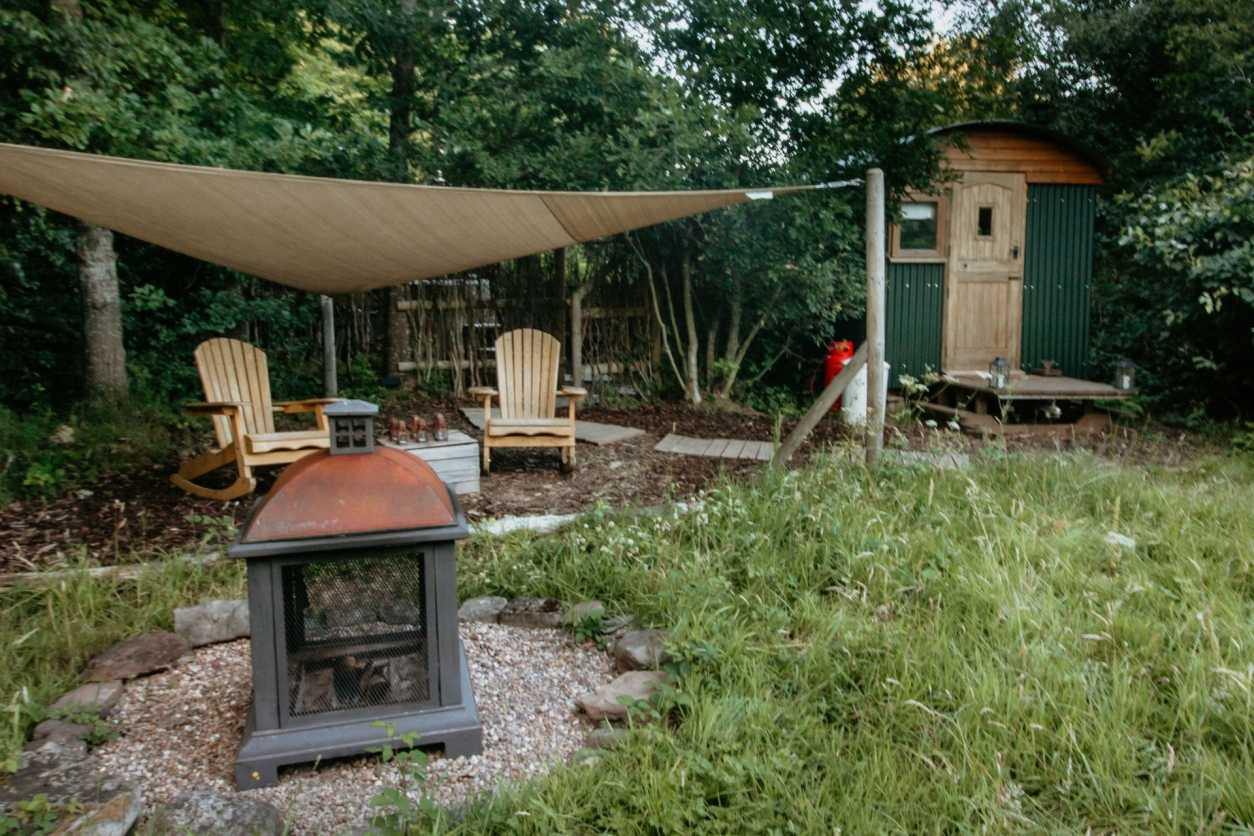 shepherds-hut-seating-area-and-fire-in-field-woodland