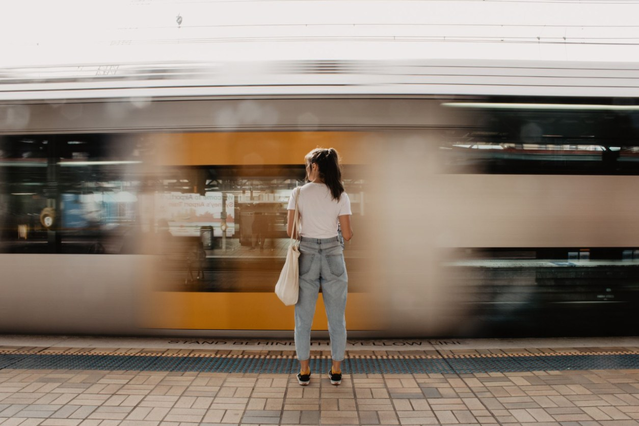 girl-wearing-a-white-t-shirt-and-baggy-light-blue-mom-jeans-standing-at-a-train-station-platform-as-a-train-rushes-past-in-the-background-interrailing-tips