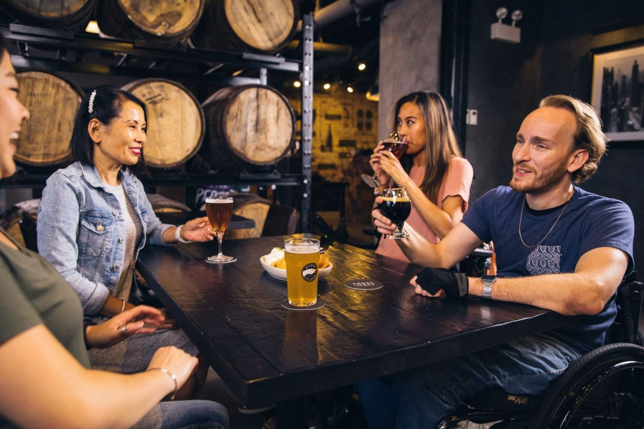 group-of-friends-enjoying-drinks-over-a-table-at-a-brewery