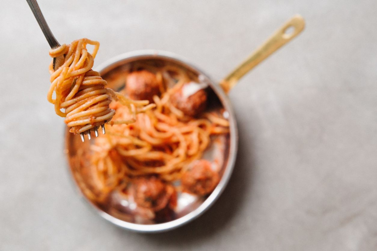 spaghetti-meatballs-in-tomato-pasta-sauce-in-pan-with-fork-above-it-with-spaghetti-wrapped-around-it