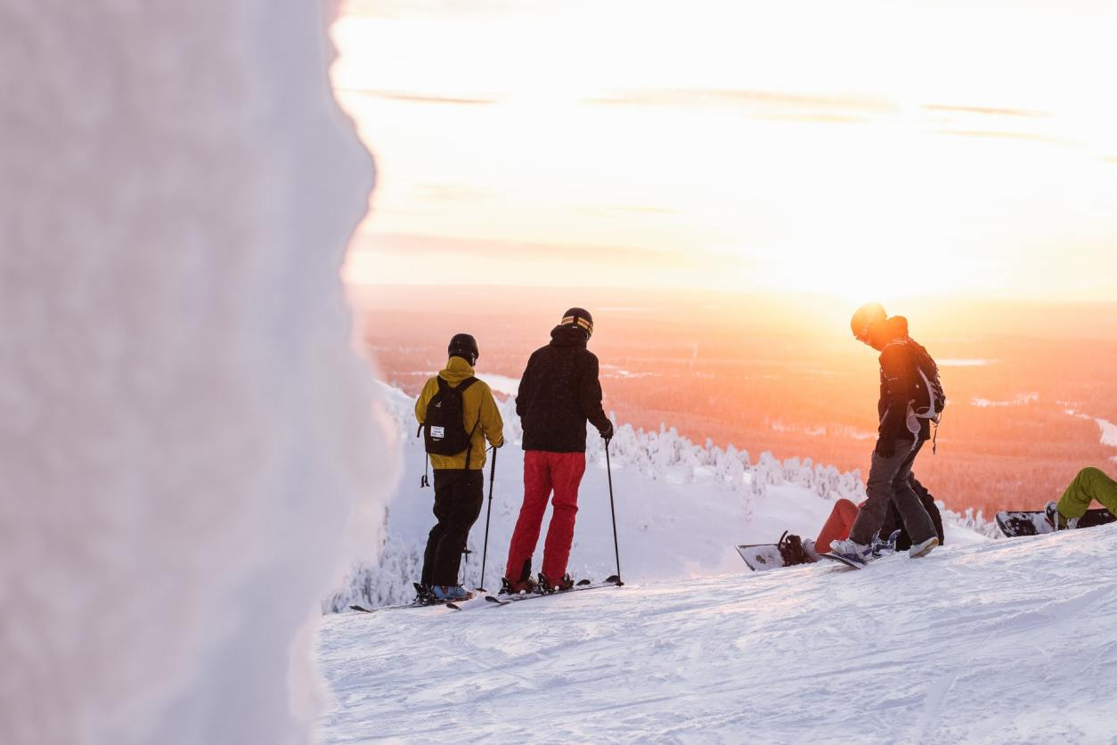 group-of-friends-up-a-snowy-mountain-with-skis-at-sunset