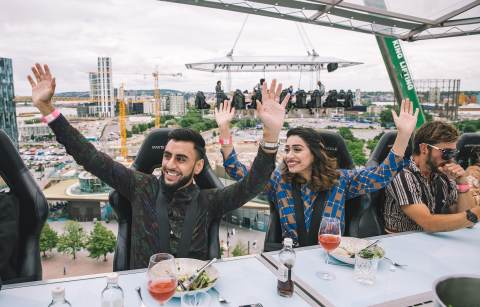 man-and-woman-with-their-arms-in-the-air-eating-dinner-in-the-sky-in-a-city-at-london-in-the-sky-quirky-places-to-eat-in-london