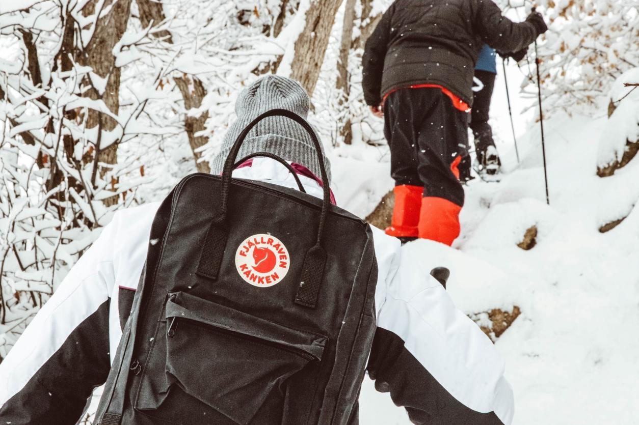 women-wearing-grey-beanie-and-fjallraven-kanken-backpack-climbing-mountain-with-walking-poles-in-snow-ski-season-packing-list
