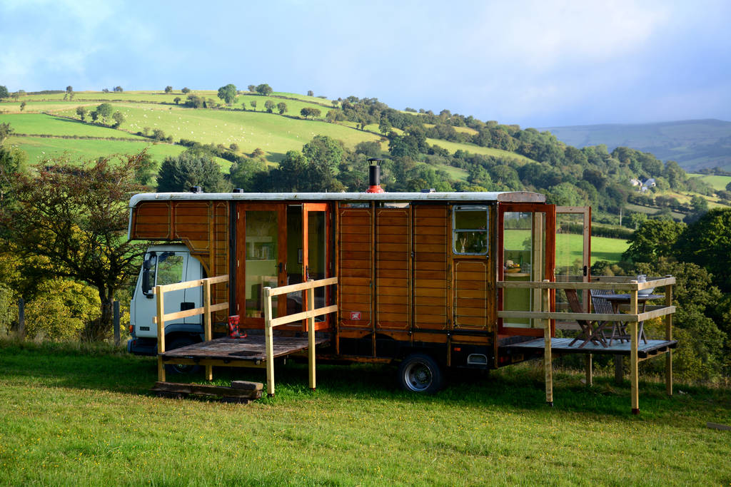 a-truck-glamping-cabin-with-decking-in-green-field-with-rolling-hills-in-background-wanderoo-pentre-naboth-in-brecon
